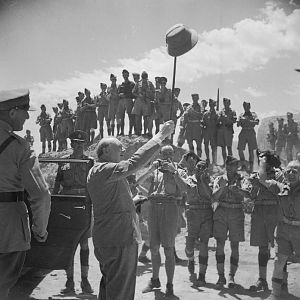 Churchill salutes allied troops in the amphitheatre at Carthage, during a visit to troops near Tunis; IWM NA 3252