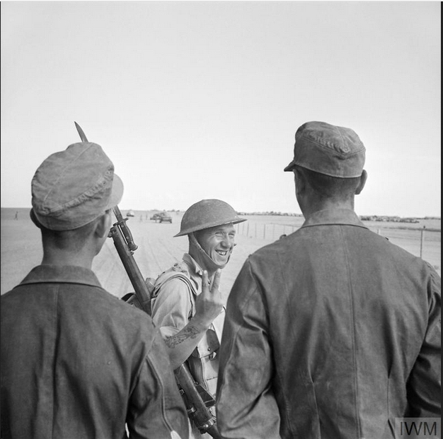 A British soldier gives a V-for-Victory sign to German prisoners captured at El Alamein, 26 October 1942
