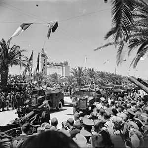 25-pdr guns and 'Quad' artillery tractors parade through Tunis, 20 May 1943; IWM NA 3021